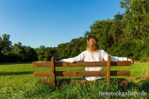 frau sitzt auf einer bank in der natur. Black Bedroom Furniture Sets. Home Design Ideas